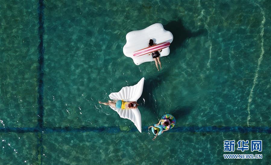 6月26日,在扬州市一水上乐园,游客戏水纳凉。近日,江苏部分地区进入高温模式。人们以水为伴,享受清凉。 新华社发(孟德龙 摄)